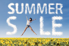Summer sale clouds and woman jumping over sunflowers Stock Photography