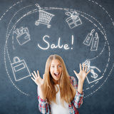 Summer sale concept. Cheerful young woman on concrete background with shopping related drawings. Summer sale concept Stock Photos