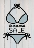 Summer sale text and blue bikini against white wood panel. Digital composite of Summer sale text and blue bikini against white wood panel Stock Photos