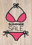 Summer sale text and pink bikini against decking. Digital composite of Summer sale text and pink bikini against decking Stock Photo