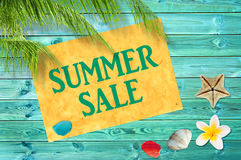 Summer sale written on yellow sign, blue wooden planks, seashells, palm tree background royalty free stock photos