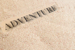 Summer sand adventure. The word adventure on a sand background with copy space Stock Photography