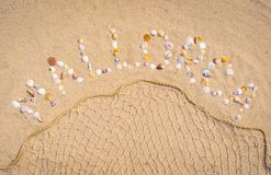 Travel to Spain Mediterranen Sea, summer beach holiday on Mallorca island. Summer sand beach with word Mallorca writing with seashells and fishing net decoration Stock Images