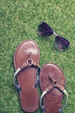 Summer sandals and sunglasses on grass. Close up of summer sandals and sunglasses on grass Stock Image