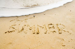 Summer sands. Word summer and picture od sun written in a sandy beach royalty free stock photography