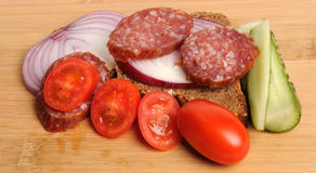 Summer sausage , bread, salted cucumber, red cherry tomatoes and sliced red onion on Bamboo cutting board Stock Image