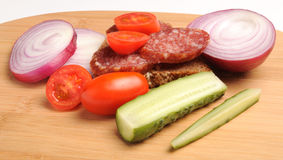 Summer sausage , bread, salted cucumber, red cherry tomatoes and sliced red onion on Bamboo cutting board Stock Photo