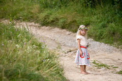Summer scene. Little girl in wild flowers wreath standing barefoot on summer road royalty free stock photo