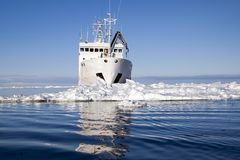 Ship surrounded by ice with reflection Royalty Free Stock Image