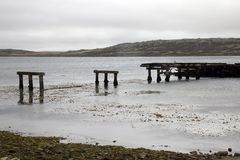 Weathered ruined pier in harbor on an overcast day stock image