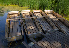 Summer scene - four wooden boats,pier,reeds,lake Royalty Free Stock Image