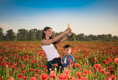 Summer scene of happy mother and son taking selfie. With smartphoneon the poppy field. Summer sunny day Royalty Free Stock Photo