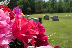 Pink and red fabric flowers in cemetery royalty free stock photography