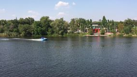 Summer scene with small boat running on a Dnepr river in center of Dnepr city, Ukraine stock video
