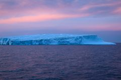 Pink sunset over iceberg stock photography