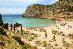 Summer scene with unidentified people in the golden beach and bl. Ue-green sea and ruins in Cala Domestica (Sardinia) in June Royalty Free Stock Images