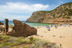 Summer scene with unidentified people in the golden beach and bl. Ue-green sea and ruins in Cala Domestica (Sardinia) in June Stock Photo