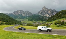 Summer scenery of Dolomiti with villages on the grassy hillside of rugged mountains & cars traveling on a highway stock images