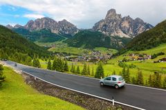 Summer scenery of Dolomiti with villages on the grassy hillside of rugged mountains & cars traveling on a highway stock photography