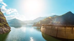 Summer scenery. of Vidraru Lake and Dam glowing in sunlight. creative image. location. Vidraru Dam, Romania. Carpathian Mountains,. Fagaras ridge. soft light stock photography