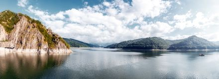 Summer scenery. of Vidraru Lake and Dam glowing in sunlight. location. Vidraru Dam, Romania. Carpathian Mountains, Fagaras ridge. Panorama of mountain lake with royalty free stock photos