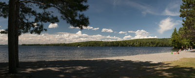 Summer scenic lake beach. Beautiful summer day at a scenic New England fresh water beach. Wide angle panorama Stock Photos