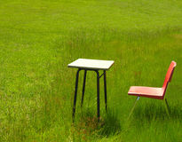 Summer school. A school desk and chair in a green meadow Royalty Free Stock Image