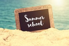 Summer school written on a vintage chalkboard in the sand, summer university concept stock image