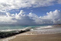Summer Sea. Ocean coast with waves, sand, and cloudy skies Royalty Free Stock Photography