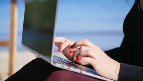 Summer,sea beach. close-up of female hands with bright red manicure, type on the laptop keyboard. working on laptop,. Summer,sea beach. close-up of female hands stock video footage