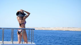 Summer, sea, beautiful young brunette woman, in a swimsuit and hat from the sun, stands on the deck of a ferry. Ship, enjoys the beauty of the sea, mountain stock video footage