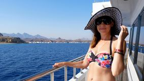 Summer, sea, beautiful sexy young brunette woman wearing a bathing suit, sun hat and sunglasses, walking along the ferry. Summer, sea, beautiful young brunette stock video