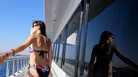 Summer, sea, beautiful sexy young brunette woman wearing a bathing suit, sunglasses, walking along the ferry deck, ship. Summer, sea, beautiful young brunette stock video
