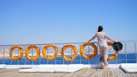 Summer, sea, beautiful young brunette woman, in a long dress and sunglasses, stands on the deck of a ferry, ship stock footage