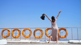 Summer, sea, beautiful young brunette woman, in a long dress and sunglasses, stands on the deck of a ferry, ship stock video