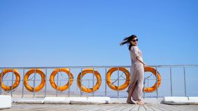 Summer, sea, beautiful young brunette woman, in a long dress and sunglasses, stands on the deck of a ferry, ship stock video footage