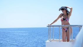 Summer, sea, beautiful young brunette woman, in a swimsuit and hat from the sun, stands on the deck of a ferry. Ship, enjoys the beauty of the sea, mountain stock footage