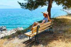 Summer sea coast  with woman on bench (Greece) Royalty Free Stock Photo