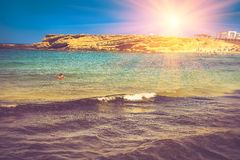 Summer sea landscape, rocky beach and swimmers at sunshine.  Royalty Free Stock Photos