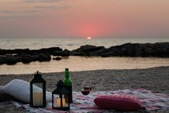 Summer sea sunset. Romantic picnic on the beach. Bottle of wine, glasses, candles, plaid and pillows. Selective focus stock image