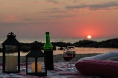Summer sea sunset. Romantic picnic on the beach. Bottle of wine, glasses, candles, plaid and pillows. Selective focus royalty free stock photo