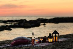 Summer sea sunset. Romantic picnic on the beach. Bottle of wine, glasses, candles, plaid and pillows. Selective focus stock photos