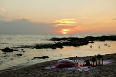 Summer sea sunset. Romantic picnic on the beach. Bottle of wine, glasses, candles, plaid and pillows. Selective focus royalty free stock images