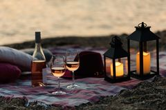 Summer sea sunset. Romantic picnic on the beach. Bottle of wine, glasses, candles, plaid and pillows. Selective focus royalty free stock photos