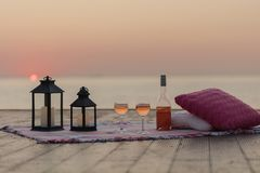 Summer sea sunset. Romantic picnic on the beach. Bottle of wine, glasses, candles, plaid and pillows. Selective focus stock images