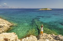 Summer seascape with blue sea and male tourist on coastline. Vacation landscape from Greece with view on a blue Ionian sea with island. Young male tourist Stock Photos