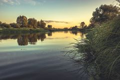 Summer season rustic countryside calm river landscape sunset with clear sky reflections riverbank in vintage style stock image