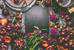 Summer seasonal various fruits and berries background frame with fruits bowls and garden flowers around blank chalkboard stock photos