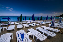 Summer seaview with deck-chairs and umbrellas Stock Image