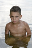 In the summer of serious  curly-haired boy is bathed in the rive Royalty Free Stock Image